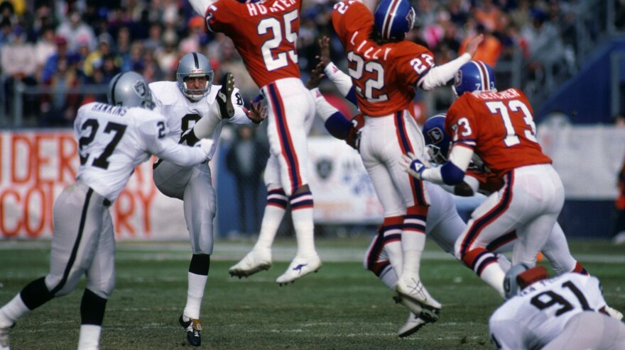 Punter Ray Guy, No. 8 of the Los Angeles Raiders, kicks the ball past the Denver Broncos' rush during a 1985 game. Guy has officially been inducted into the Pro Football Hall of Fame.