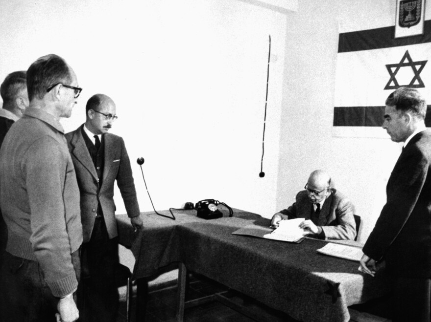 Adolf Eichmann (far left) in an Israeli courtroom, March 9, 1961, where papers were signed automatically extending his detention.