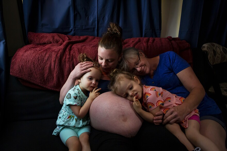 Chelsea Isaacs sits on the couch in her RV with her 2-year-old twin daughters, Harper and Riley, and her mother, Kim Schwartz, on June 11 in Magalia, Calif. They have been living for almost a year in an RV after the Camp Fire destroyed their home in 2018. A month after their house burned down, Chelsea found out she was pregnant with a second set of twins with her partner, Noah.