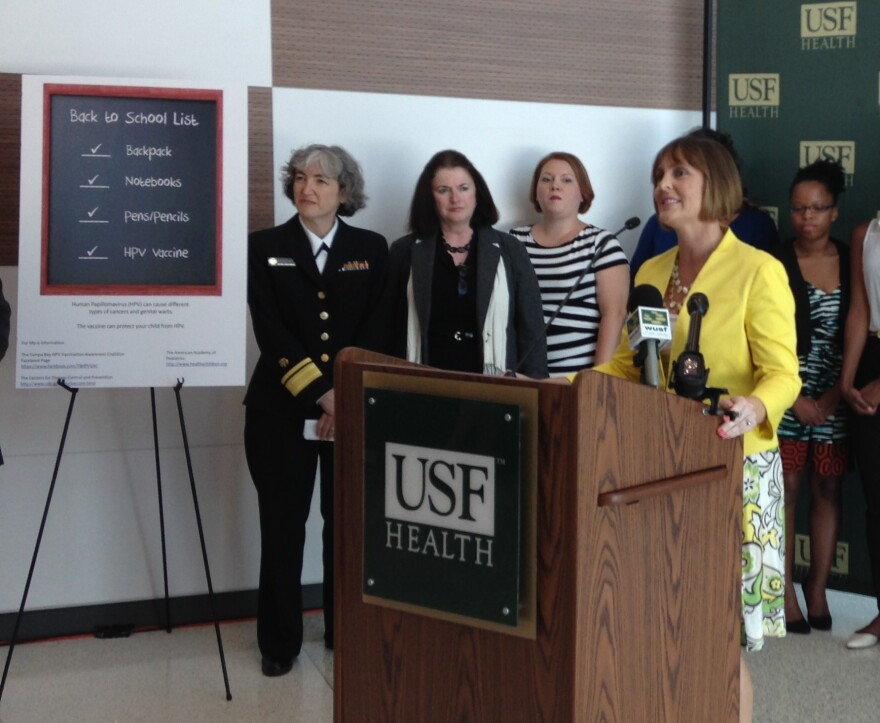 Dr. Anne Schuchat, left, stands next to a poster promoting HPV vaccination. The poster and other education materials were created by USF Public Health graduate students.