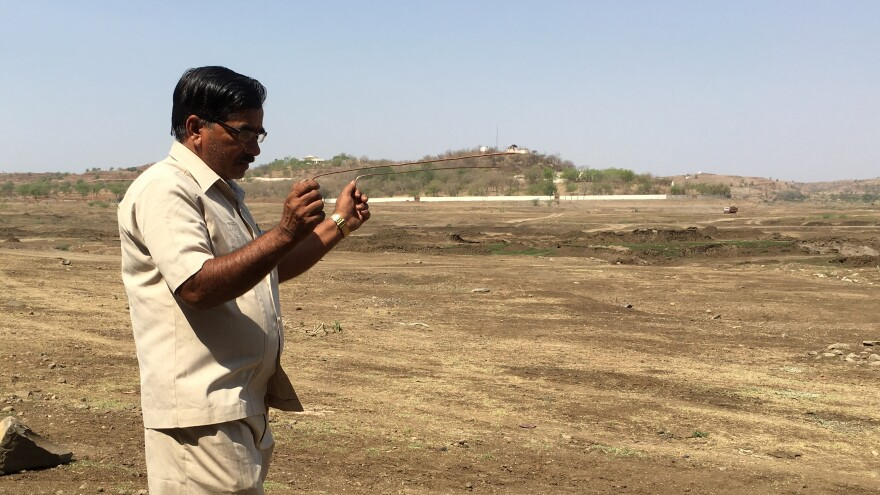 Ambadas Raut uses copper rods known as dowsing sticks to locate sources of underground water in a dry reservoir. He's had 400 clients and says he's found water for 80 percent of them.