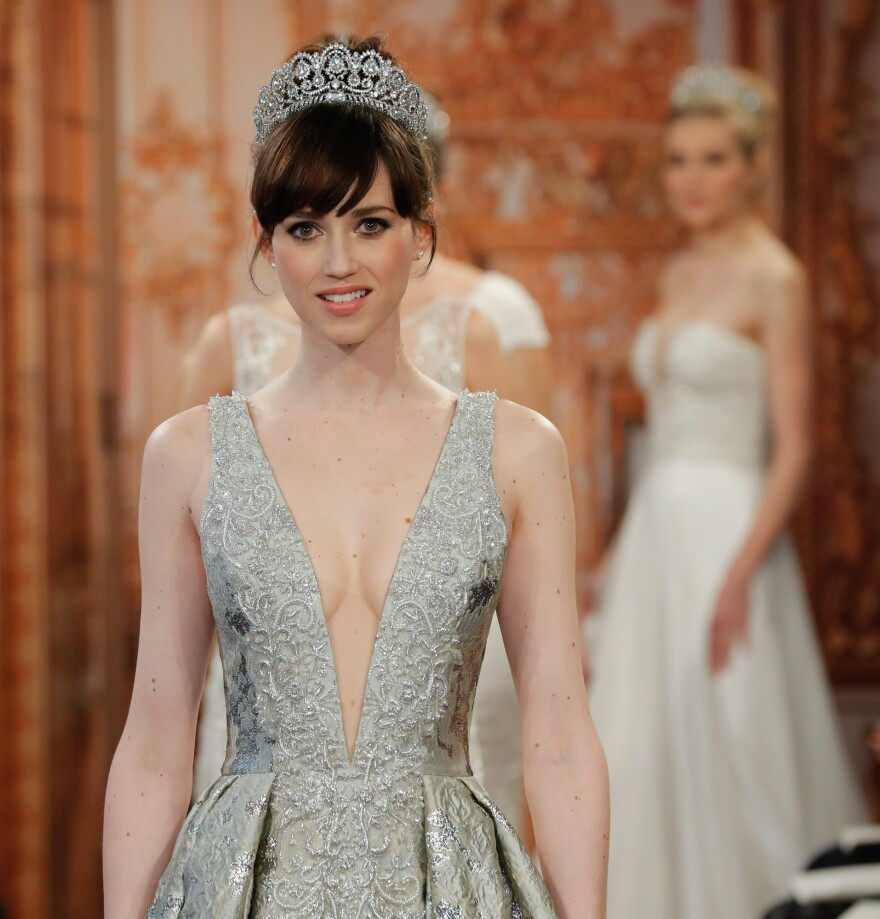 A model walks the runway in a low cut gown at this year's Bridal Fashion Week in New York.