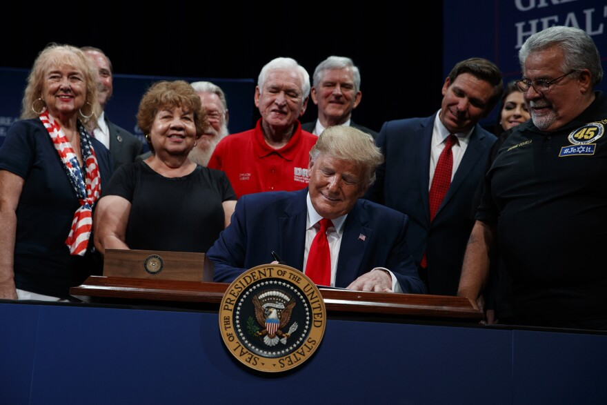 President Donald Trump signs an executive order about Medicare at the Sharon L. Morse Performing Arts Center, Thursday, Oct. 3, 2019, in The Villages, Fla. President Donald Trump signs an executive order about Medicare at the Sharon L. Morse Performing Ar