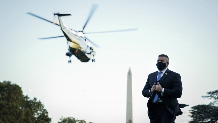 A U.S. Secret Service agent stands on the South Lawn of the White House as Marine One, with the president on board, leaves Friday for Walter Reed.