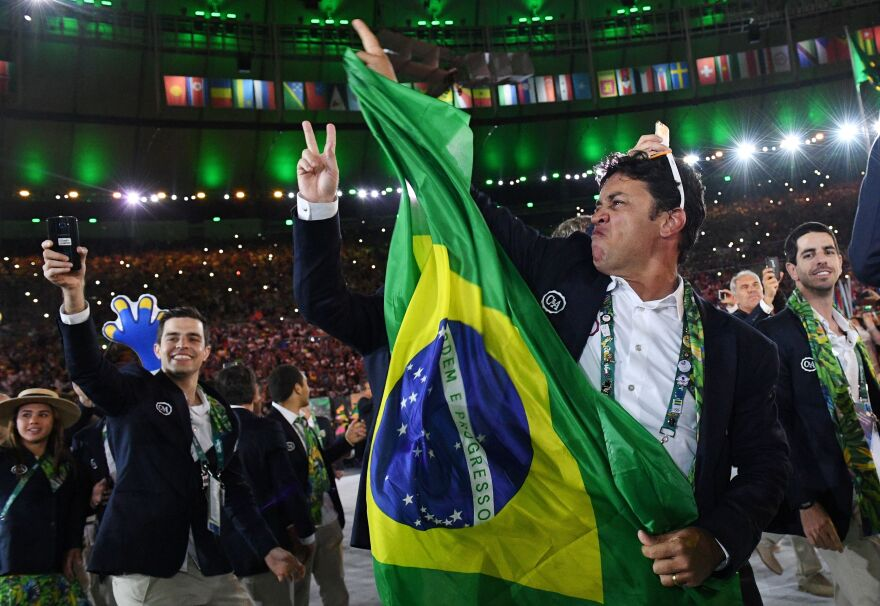 "A member of the Brazil delegation waves a flag. The athletes and staff are dancing as a long remix of the classic 1939 song ""Aquarela do Brasil"" — known to many English-speakers simply as ""Brazil"" — plays."