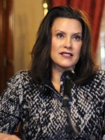 """Michigan Gov. Gretchen Whitmer addresses the state during a speech in Lansing, Mich., on Monday. Whitmer says she's listening to """"the best medical advice"""" on when to ease restrictions."""