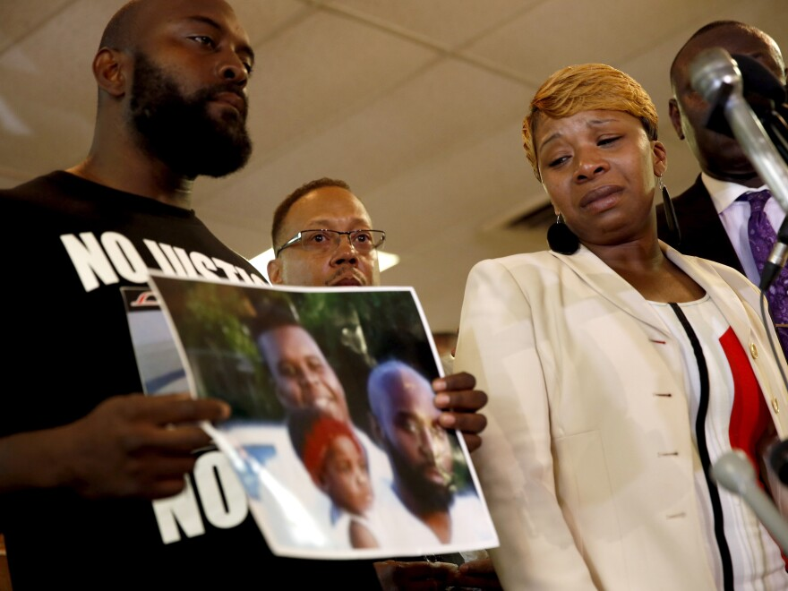 Lesley McSpadden, right, the mother of 18-year-old Michael Brown, watches as Brown's father, Michael Brown Sr., holds up a family picture of himself, his son, top left in photo, and a young child during a news conference Monday, Aug. 11, in Ferguson, Mo.