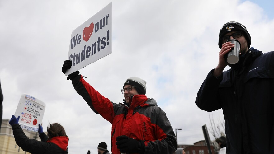 West Virginia teachers, students and supporters hold their signs aloft during a demonstration earlier this month in Morgantown, W.Va.