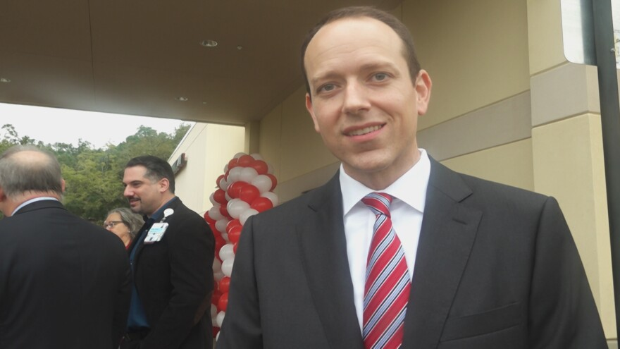 Man in suit and tie smiles at the camera. Behind him are people smiling.