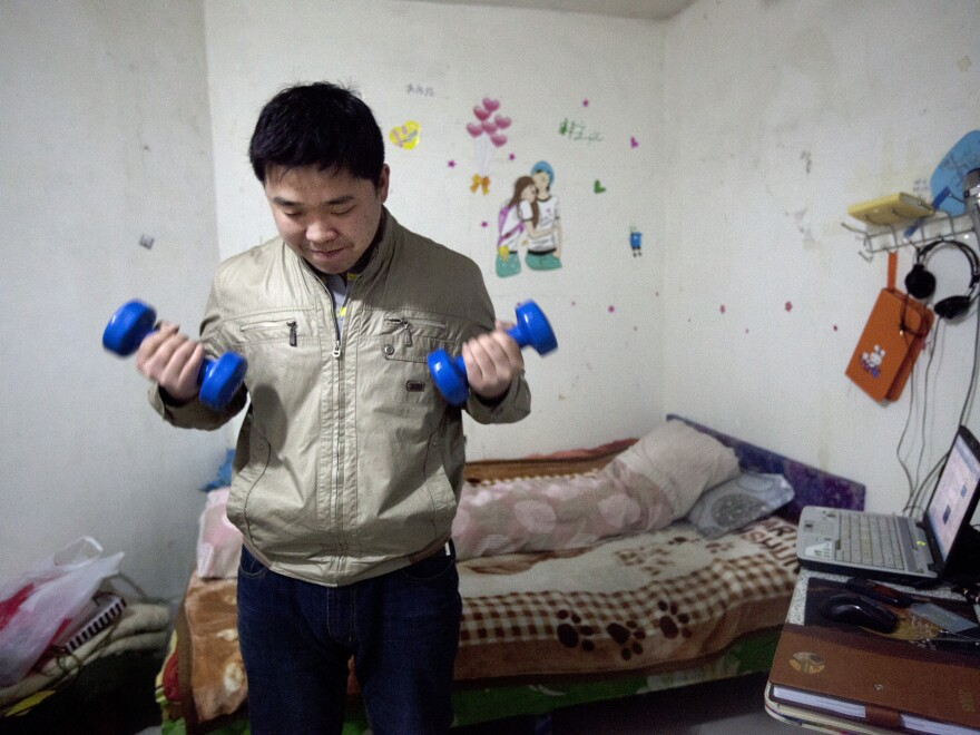 Xie Jinghui sometimes does some weightlifting in his basement room. Photographer Sim Chi Yin says people adapt to these close quarters.