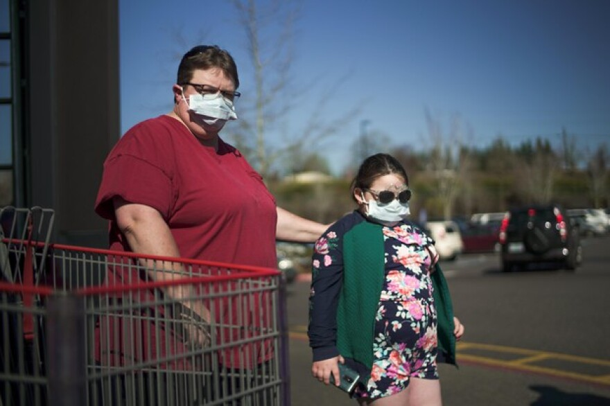 Customers wearing face masks exit Costco in Tigard, Oregon, March 20, 2020.