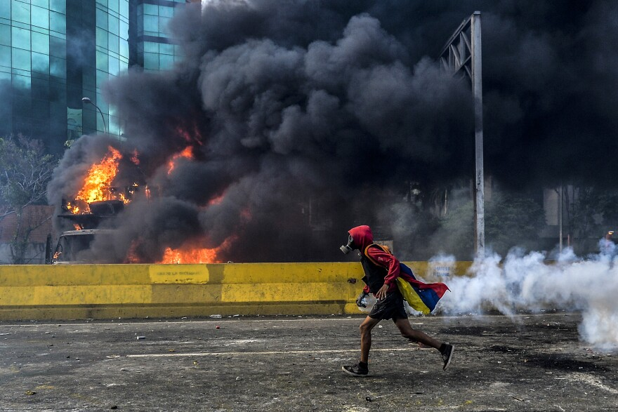 An anti-government protester runs past a burning truck blocking the Francisco Fajardo Highway in Caracas on Saturday. The demonstrations across Venezuela are entering their third month.