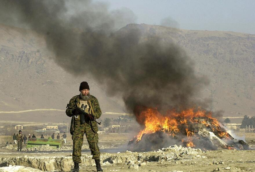 An Afghan policeman stands guard as an 8-ton pile of opium, heroin and hashish is destroyed in Kabul in 2004.