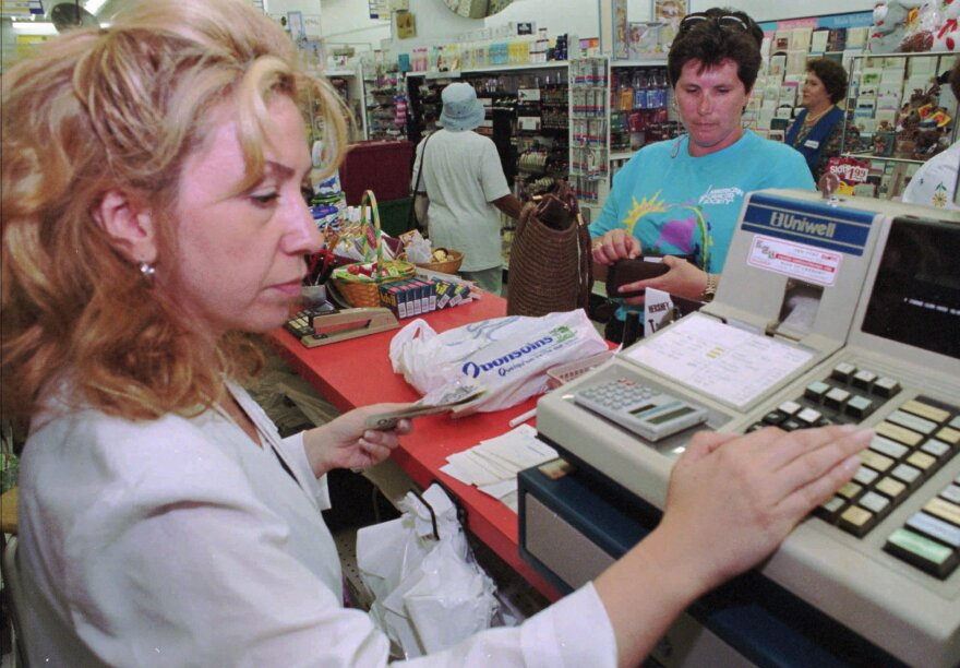Woman is typing numbers into a cash register. A woman in front of her has her wallet out to give the cashier money.