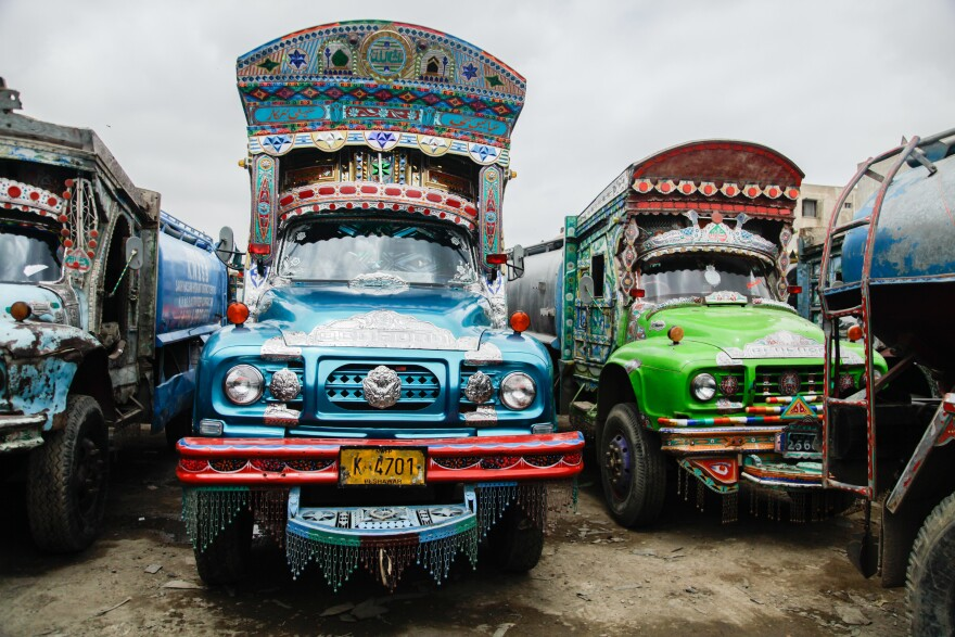 Shiny, decorated, colorful water tankers park near a hydrant in Karachi, Pakistan.