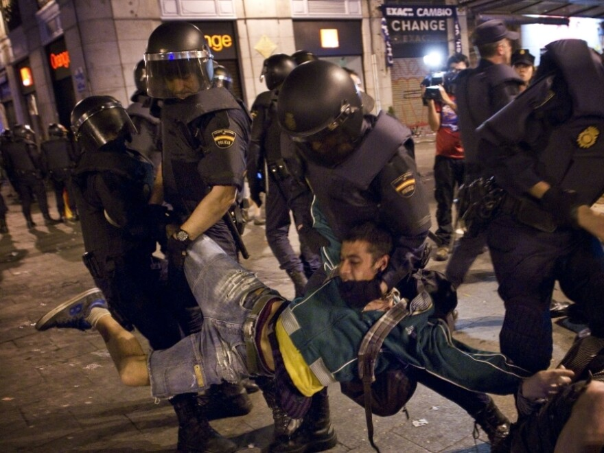 Spanish police officers carry off a demonstrator as he and others are evicted from a square in Madrid on Sunday.