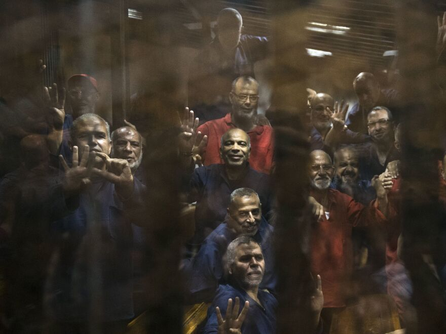 Egyptian Muslim Brotherhood defendants stand behind bars in Cairo last year during their trial, along with Mohammed Morsi, the former president who was ousted in 2013. Egypt's jails historically have bred militancy.