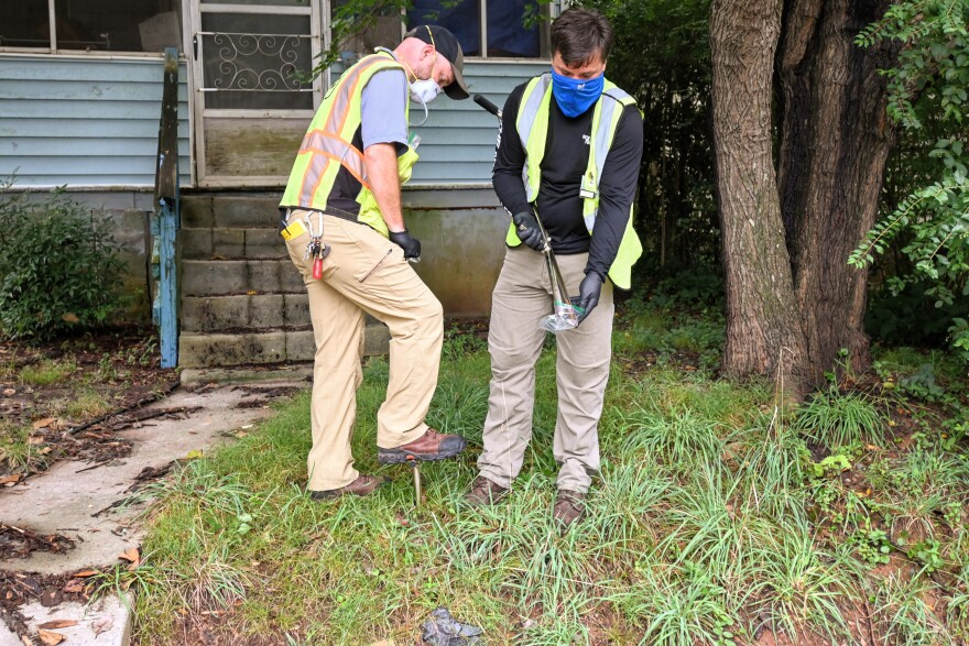Contractors for the EPA take soil samples at a house on the West Side of Davidson Tuesday.