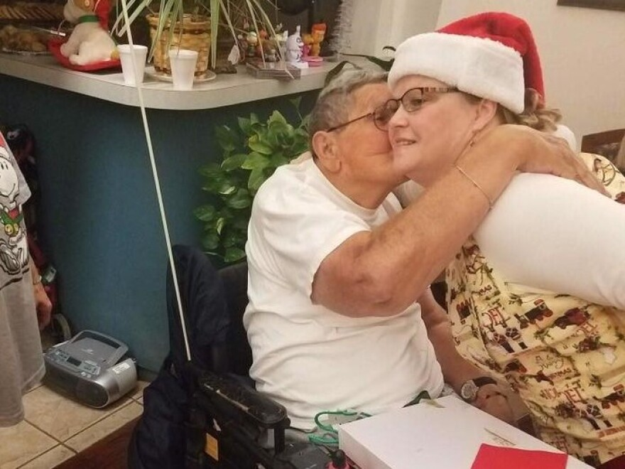 A resident of the Cordell Christian Home in Cordell, Okla., kisses Mrs. Claus at the annual holiday party in 2017.