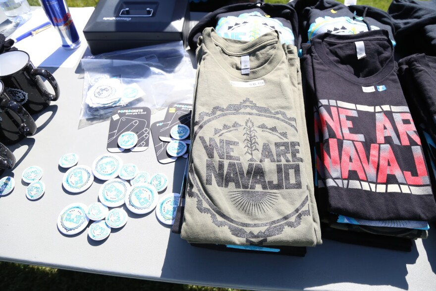 """A photo of t-shirts and buttons that say """"We are Navajo"""" on a table."""