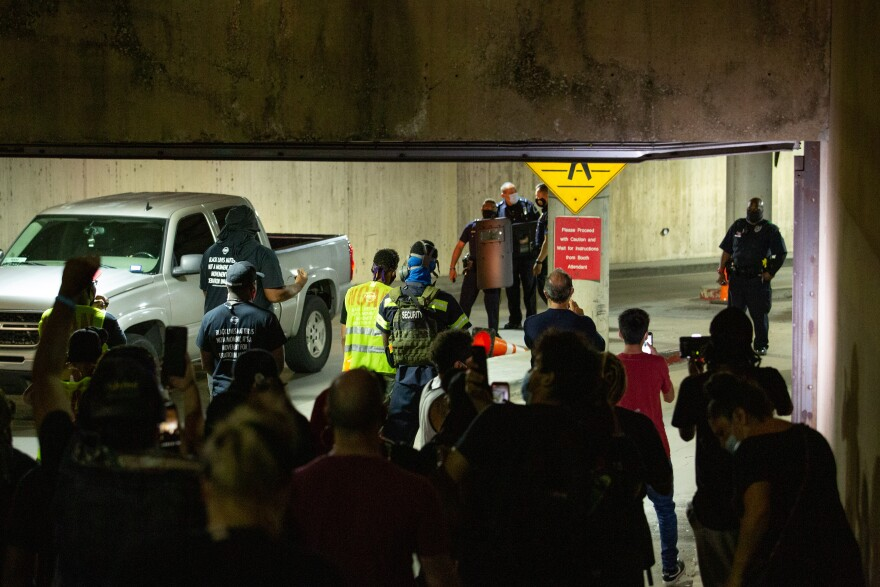 Photo of  Dallas police with crowd control shields encountering protesters in the Dallas City Hall parking garage.