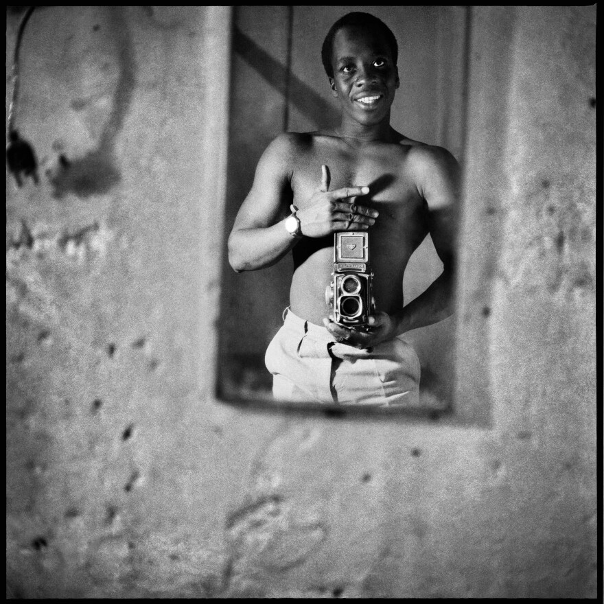 "Sanle Sory took ""autoportraits"" as in this selfie showing off his Rolleiflex camera. He was born in 1943 in what was still colonial Upper Volta and is now the country of Burkina Faso. His black-and-white portraits show the old meeting the new: families posing in Western garb, young people side by side with a boom box and a traditional African stringed instrument."