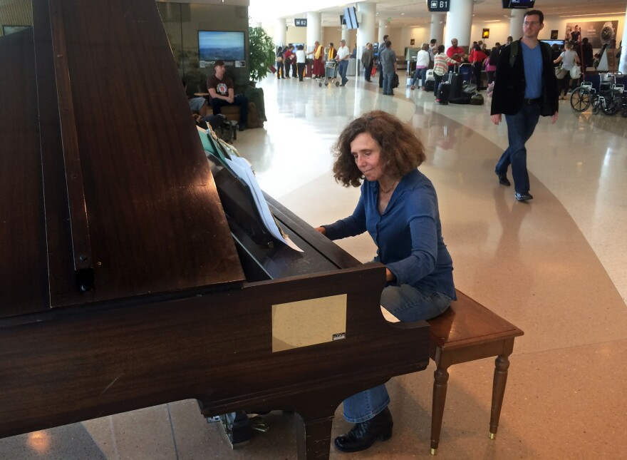 Sara Solovitch plays the piano in the Terminal B baggage claim area at San Jose International Airport.