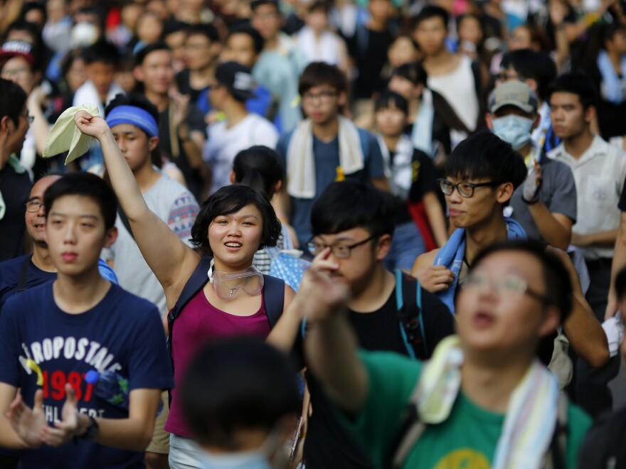 Protesters march as they block the main street to the financial Central district, outside the government headquarters in Hong Kong, on Monday. Protesters at times numbering in the tens of thousands have gathered to demand the right to choose the territory's next leaders.