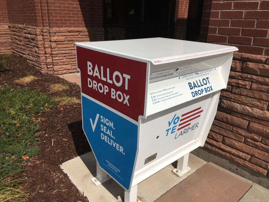 """A ballot drop box in Larimer County. """"Sign. Seal. Deliver."""" is written on the side."""