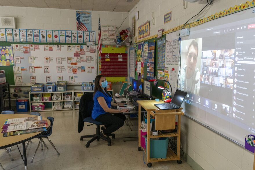 Kindergarten teacher Christine Figueroa wears a mask as she watches a gym class where her students are participating remotely and in person at school in Oct. 2020 in Yonkers, New York. (Mary Altaffer/AP)