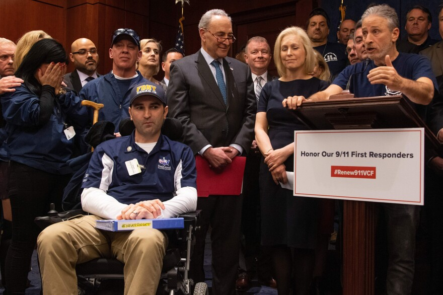 """Former """"Daily Show"""" host Jon Stewart (right) with Senate Minority Leader Chuck Schumer (center), D-N.Y., Sen. Kirsten Gillibrand (second right), D-N.Y., and 9/11 first responders, survivors and their families to discuss the introduction of the bipartisan """"Never Forget the Heroes: Permanent Authorization of the September 11th Victim Compensation Fund Act."""" (Jim Watson/AFP/Getty Images)"""