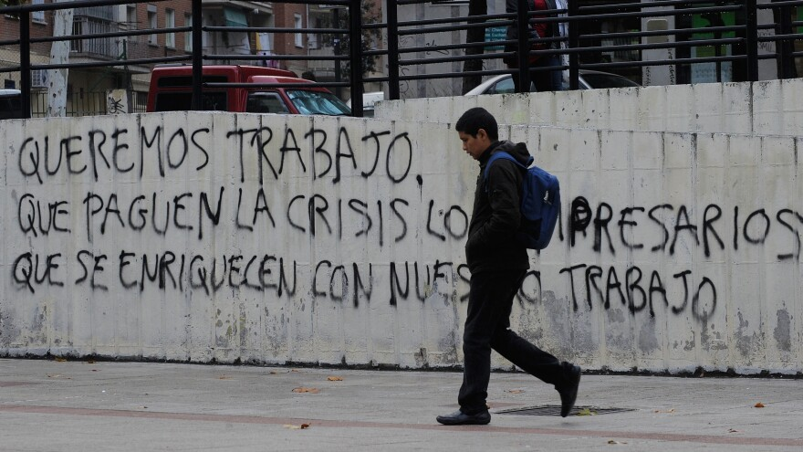 """Graffiti on a wall in Madrid reads, """"We want to work, let the businessmen who have gotten rich from our labor pay for the crisis."""" Nearly 50 percent of young adults in Spain are unemployed."""