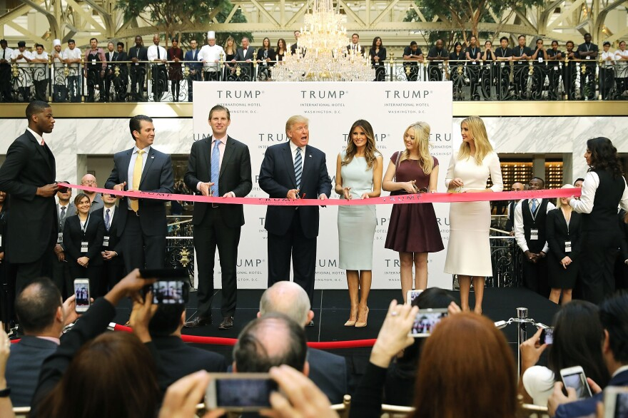 Donald Trump, center, then the Republican presidential nominee, attends the opening of the Trump International Hotel in Washington, D.C., in October 2016. After winning the election, Trump did not divest himself of his business holdings or put them in a blind trust. Lawsuits have been filed that allege he is violating anti-corruption provisions in the Constitution.