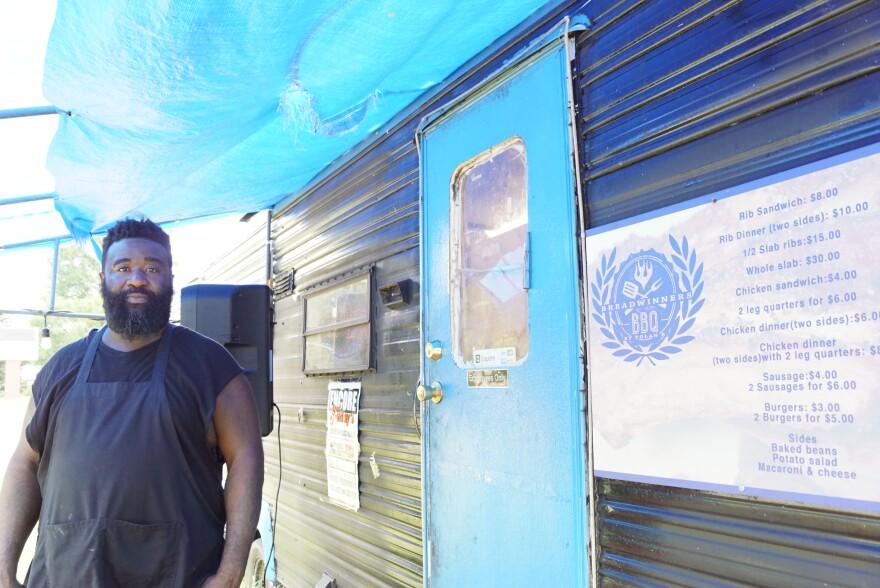 man in black t-shirt standing next to food truck with blue door