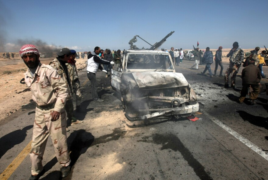 Libyan rebels stand next to two destroyed loyalist pick-up trucks after they were hit by a NATO airstrike on the outskirts of Brega on Tuesday.