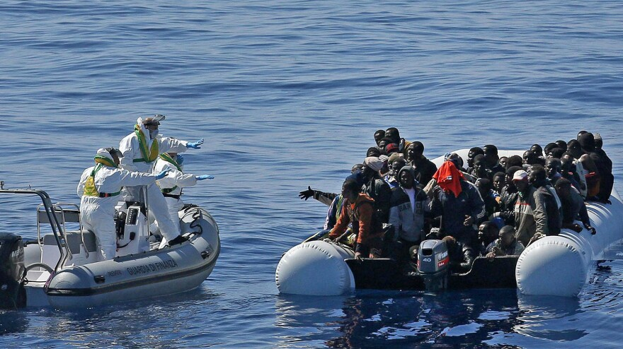 In this photo made available Thursday, April 23, 2015, migrants crowd and inflatable dinghy as the Italian Coast Guard approaches them, off the Libyan coast, on Wednesday.