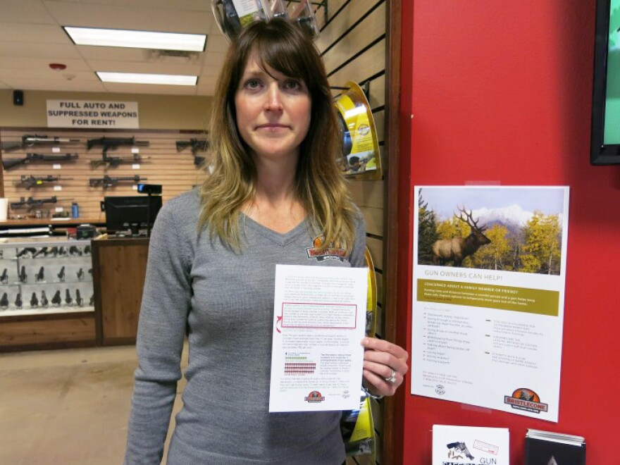 """Jacquelyn Clark, co-owner of Bristlecone Shooting, Training and Retail Center in Lakewood, Colo., holds a list of gun safety rules. One recommendation: Consider """"off-site storage if a family member may be suicidal."""""""
