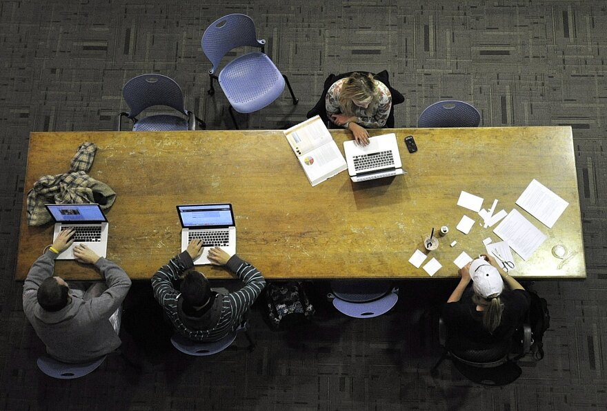 Overhead shot of four students studying around a long, wooden table.