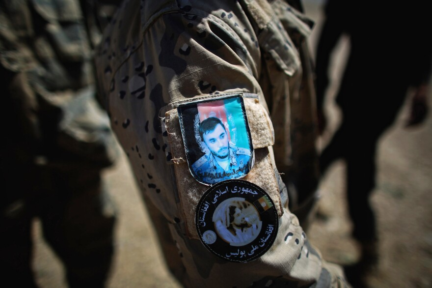A patch on an Afghan National Police officer's uniform features the face of Raziq.