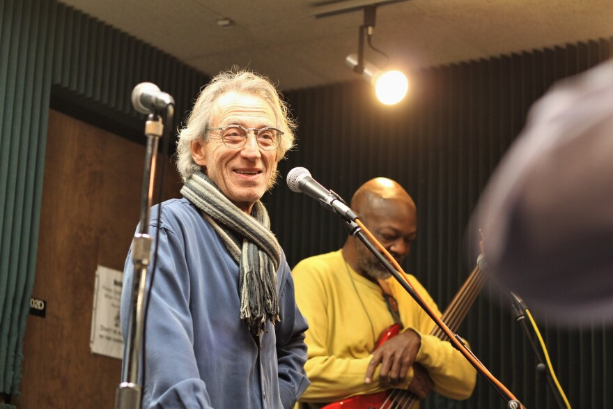 A white haired man with a scarf on stands in front of a microphone. A black man in a yellow shirt stands behind him with a guitar.