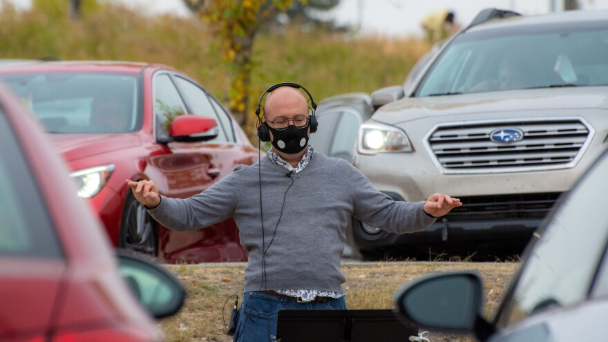 Schantz conducts Luminous Voices' first car concert, on Oct. 4, 2020. Audience vehicles are seen parked to behind him.