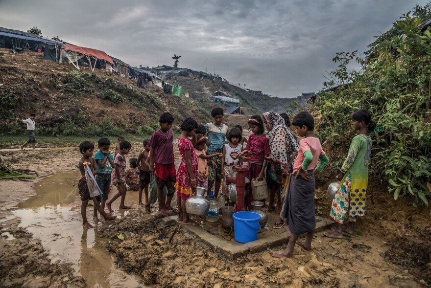 Rohingya refugees collect drinking water from a pump in a camp in Bangladesh.
