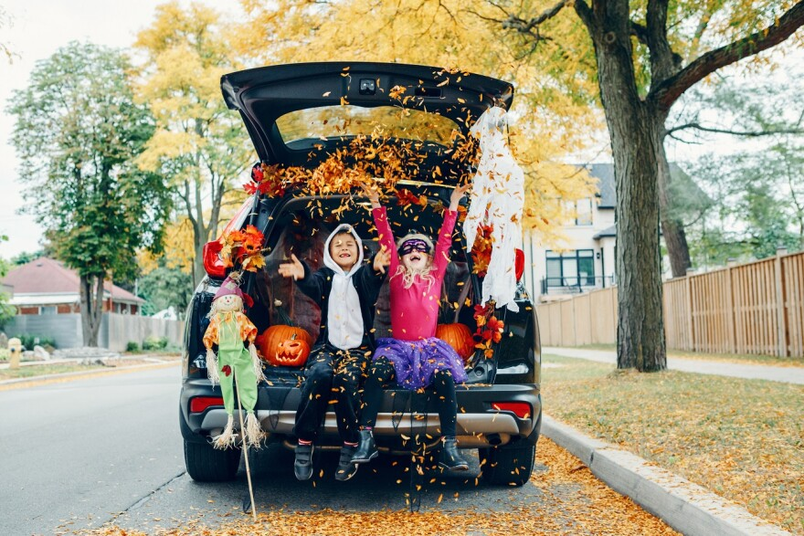 Trick or trunk. Children celebrating Halloween in trunk of car. Boy and girl with red pumpkins celebrating traditional October holiday outdoors. Social distance during coronavirus covid-19.