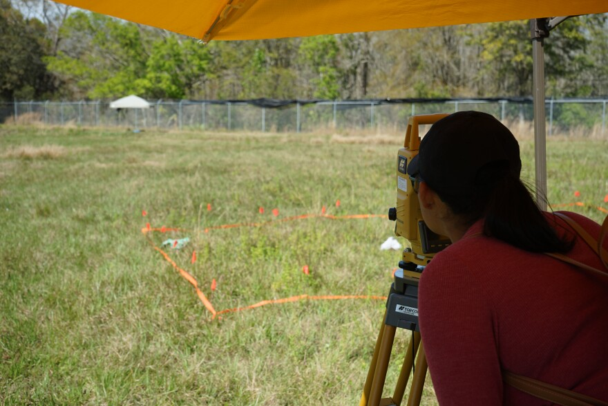 A student uses total station surveying equipment to study the mock crime scene.