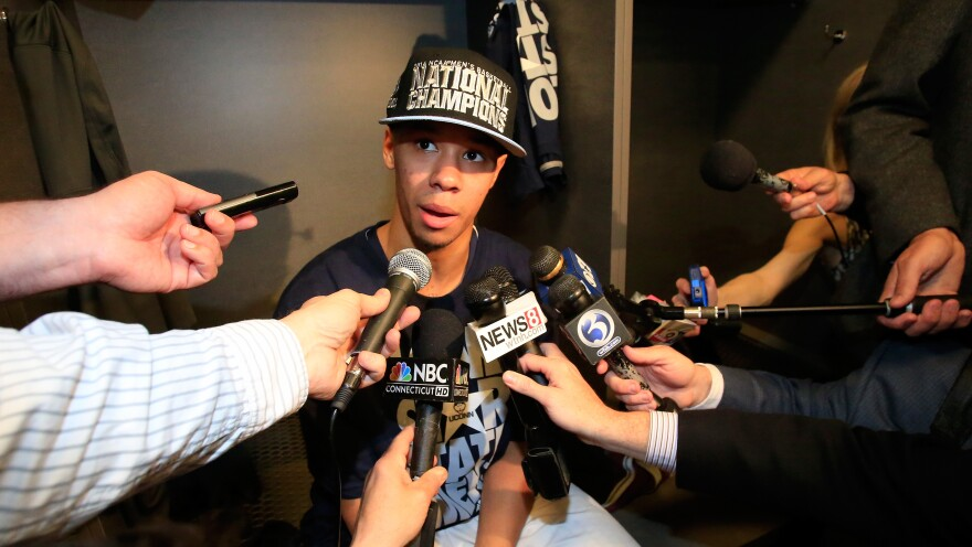 Shabazz Napier of the Connecticut Huskies speaks to the media in the locker room after defeating Kentucky in the NCAA men's championship on April 7.