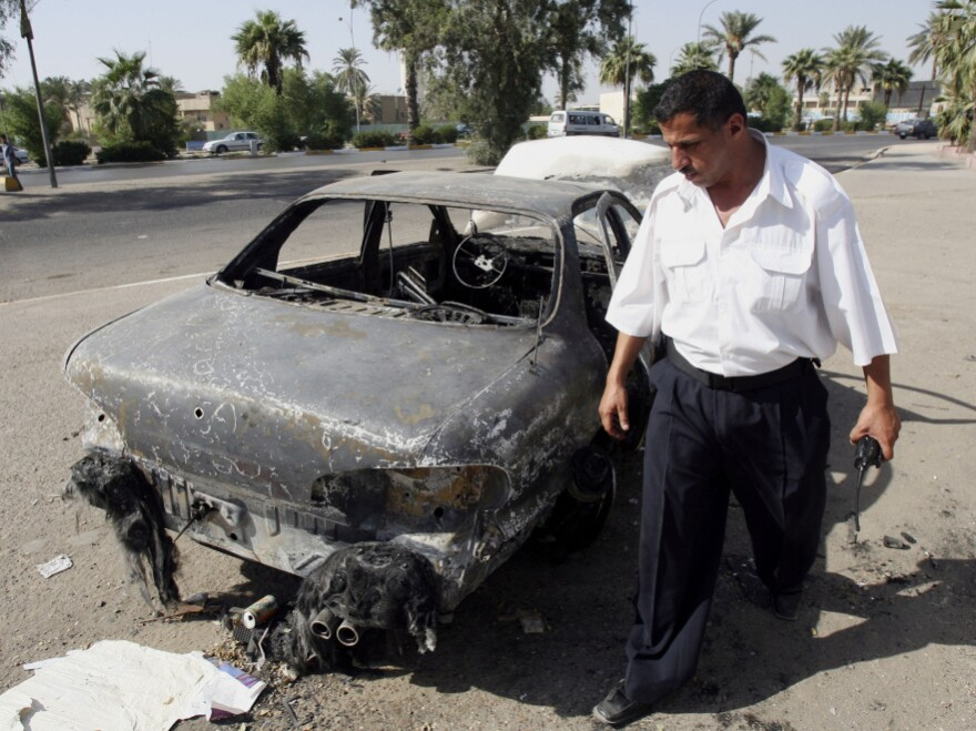 Sept. 20, 2007, file photo: An Iraqi traffic policeman inspects a car destroyed during the firefight four days earlier in Baghdad's al-Nisoor Square.