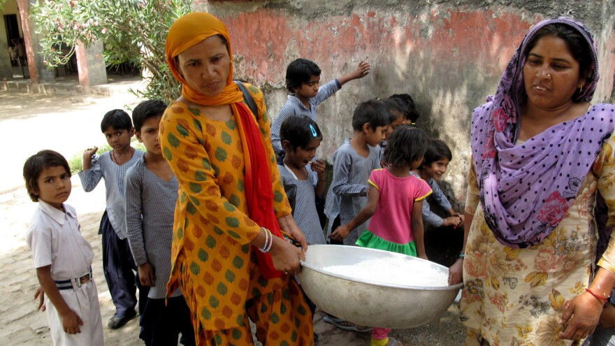 Saroj (left) helps her colleague carry a cauldron of rice to the school kitchen after washing it.