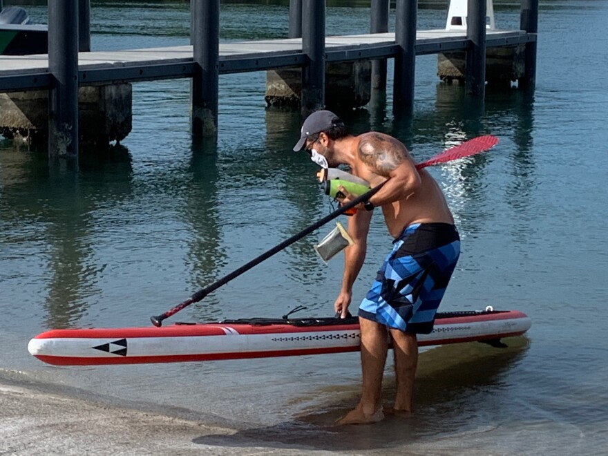 Fabio Kern went paddle boarding at Crandon Park on Wednesday when some parks reopened across South Florida. He said he has been furloughed from his job and stuck at home for weeks.