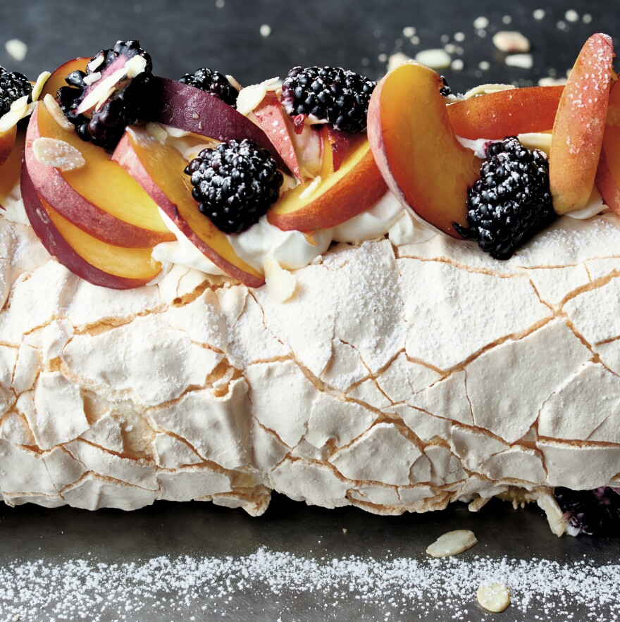 Pavlova is a meringue filled with cream and fruit. Chef Yotam Ottolenghi covers his with seasonal fruit. The version pictured above features summer peaches. For the holiday season, he suggests using plums and blackberries.