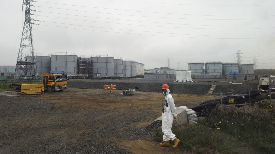 A construction worker walks beside underground water tanks at the Fukushima Daiichi nuclear plant in Japan.